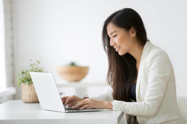 ノートPCでブログを書く女性