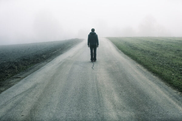 霧がかかった道を歩く男性