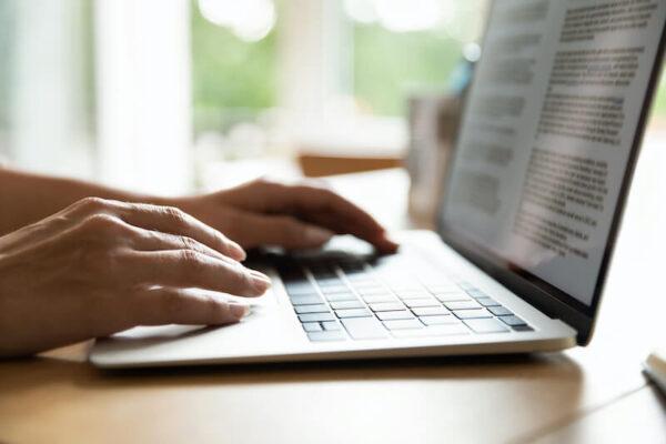 ノートパソコンでテキストを入力する女性
